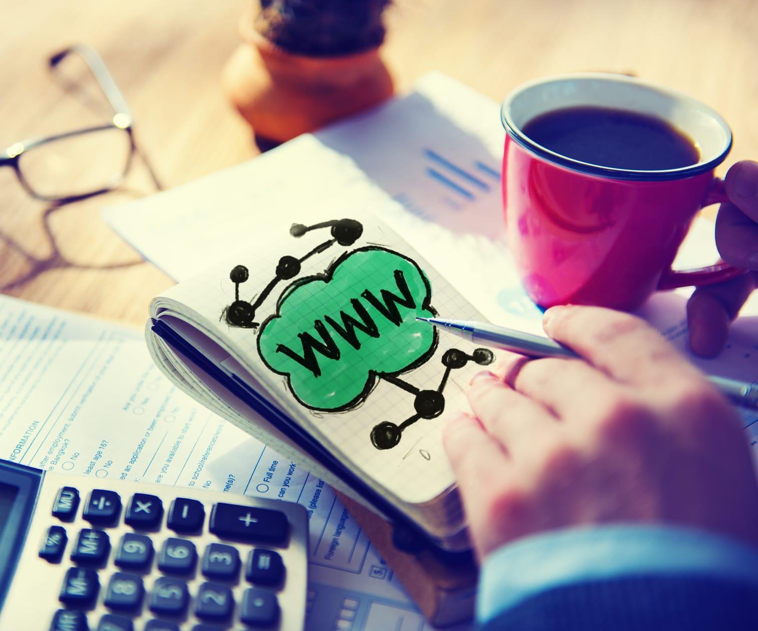 une main pointe un stylo sur le sigle www dessiné sur un carnet