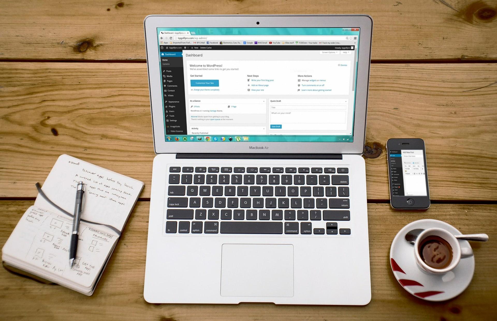 Un PC portable ouvert sur le panel administration de Wordpress, un café crème, un smartphone ouvert aussi sur le panel de wordpress et un carnet de note.